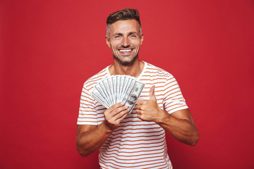 Photo of brunette man in striped t-shirt smiling and holding fan of money in cash, isolated over red background