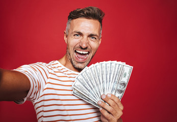 Photo of delighted man in striped t-shirt smiling and taking selfie while holding fan of money banknotes, isolated over red background