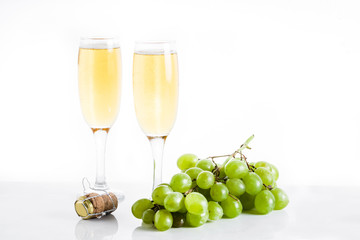 Champagne glasses and green grapes on white background