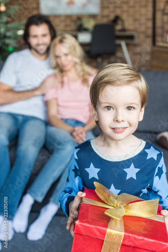 adorable happy child in pajamas holding christmas present and smiling at  camera while parents sitting behind 81c35845d