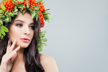 Beautiful woman with natural makeup, perfect skin, healthy hair and green leaves on background with copy space