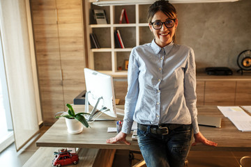 Portrait of mid age business woman.She standing in her office and looking at camera.