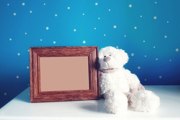 Empty photo frame and white Teddy bear in the beautiful blue starry nursery