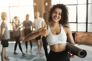 Woman ready for workout with yoga mat and thumb up