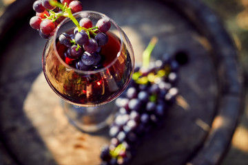 Close up of a glass of red wine on a wooden barrel with grapes