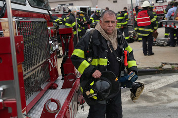 A FDNY firefighter makes his way back from working a seven-alarm fire in Brooklyn
