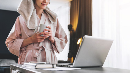Pretty woman in bathrobe using laptop at table with partner in background at home in the kitchen