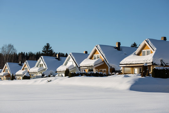 a row of little wooden houses covered with a thick snow layer, deep untouched white snow around