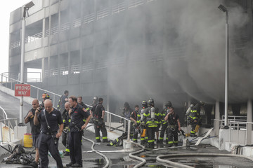 Firefighters work at the scene of a seven-alarm fire at the Kings Plaza Shopping Center in New York