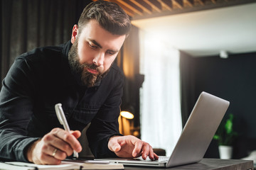 Businessman is standing near computer, working on laptop, making notes in notebook. Man watching webinar, learning.