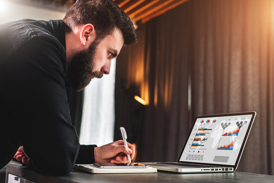 Businessman is looking at laptop screen while making notes in notepad. Entrepreneur analyzes information, compares data.