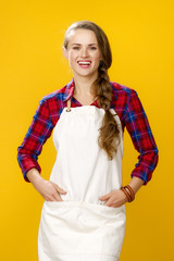 happy young woman farmer wearing apron isolated on yellow