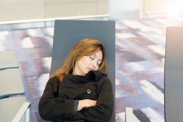 Asian beauty women Sleeping at the airport terminal Because the plane was delayed. and waiting fot airplane arrival