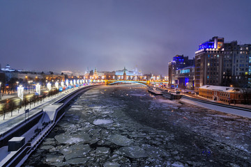 View of Moscow Kremlin and Bolshoy Kamenny Bridge from Patriarshy Bridge at night in winter. Moscow. Russia