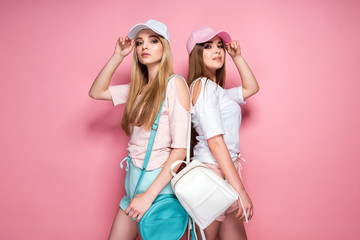 Side view of two beautiful women with bags, caps while standing on pink background Wall mural