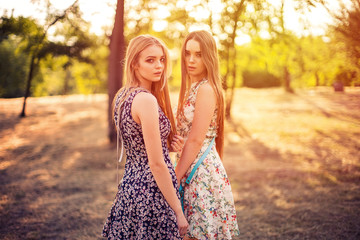 Side view of two lovely young ladies looking at camera while standing in beautiful park on sunny day together