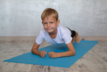 European boy with a smile performs plank exercise on the Mat