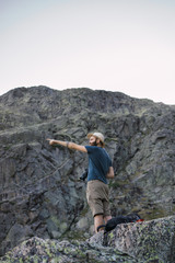 Young man standing on rock and taking picture