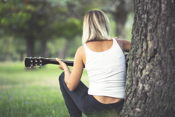 A young female playing guitar outdoors
