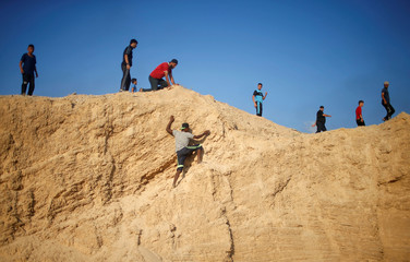 Palestinian demonstrator climbs a hill during a protest calling for lifting the Israeli blockade on Gaza, near the maritime border with Israel, in the northern Gaza Strip