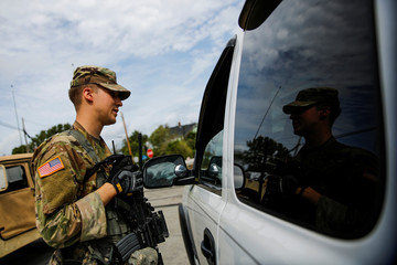 U.S. Army soldier asks for documents to a driver as he stands guard near an affected area due to flooding caused by Hurricane Florence, now downgraded to a tropical depression in New Bern, North Carolina