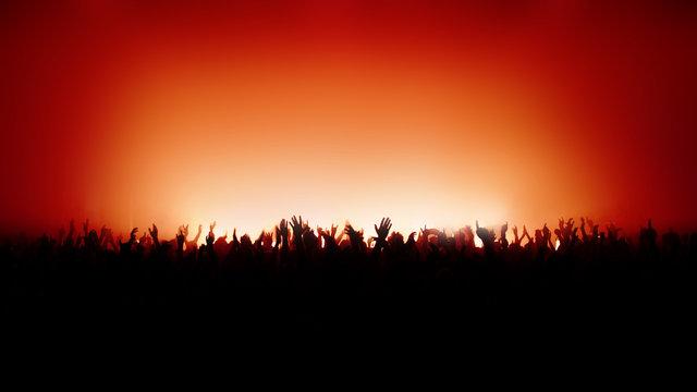 Jubelndes Publikum bei Konzert in rotem Licht