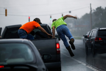 People jump out of a truck to cover themselves from rain caused by Hurricane Florence, now downgraded to a tropical depression in New Bern, North Carolina