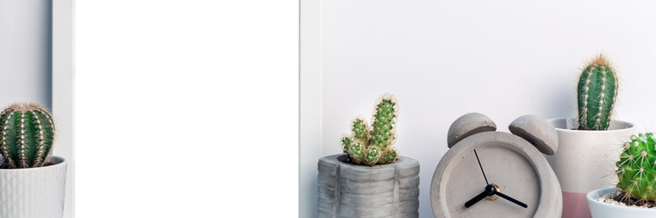 Panoramic photo of desk with a white frame mockup, cactuses and a concrete alarm clock