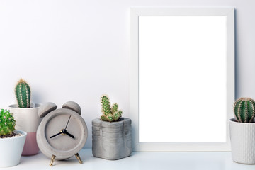 Desk with a white frame mockup, cactuses and a concrete alarm clock