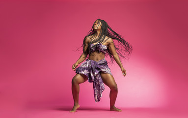 Photo Blinds Dance School Beautiful African Black girl wearing traditional colorful African outfit does a dramatic dance move against a colorful pink background
