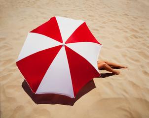 Woman lying on sand under umbrella