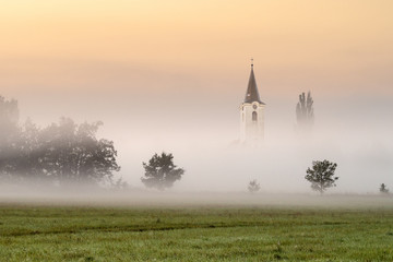 Small church in the foggy landscape.