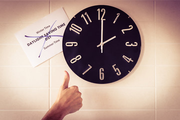 Big black clock on white wall. Time change. DST. Survey of the European Union on time change. Gesture of agreement. Thumb up of Caucasian man. Banner with text. English