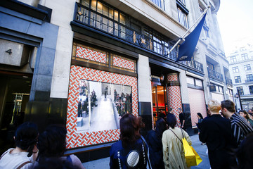 People watch a Burberry catwalk show broadcast on screens at the Burberry store on Regent Street, London