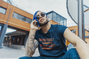 Young attractive man with blue dreadlocks talking by mobile phone and touching his hair.