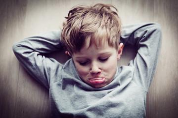 little boy feels annoyed grumpy lying on the floor