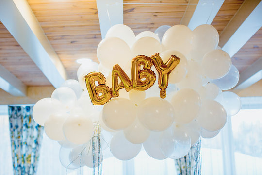 Festive decoration for birthday of baby, many white balloons