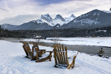 Winter Landscape View of Wooden Adirondack Chairs in snow by Bow River with distant Three Sisters Mountains above City of Canmore in Alberta Foothills