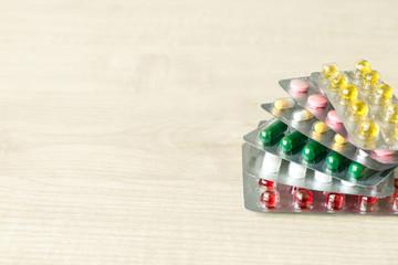 Pharmaceuticals antibiotics pills capsule medicine.  Stack  of different colorful antibacterials pills and capsule on wooden background