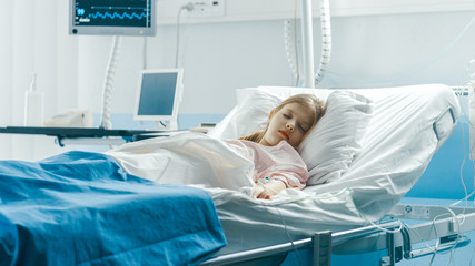 Cute Little Sick Girl Sleeps on a Bed in the Children's Hospital. Modern Pediatric Ward with Top Quality Health Care.
