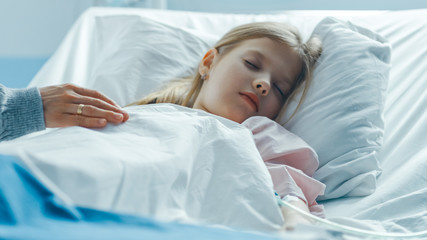 Cute Little Girl Sleeps on a Bed in the Children's Hospital, Caring Mother Covers Her with a Blanket and Caresses Her Forehead. Modern Pediatric Ward with Top Quality Health Care.