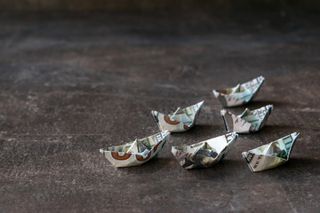 Origami ships from US dollars on a dark background. Many boat dollar banknote. Cash, money flow, Financial, Currency economic concept