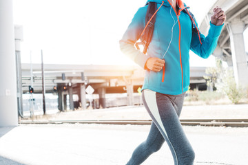 Sporty woman running in city industrial area