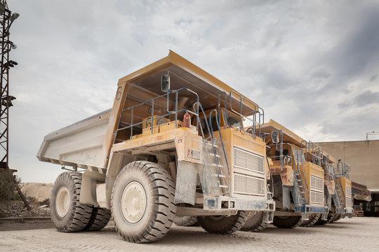 Big yellow dump trucks in the stone quarry. Mining trucks, mining machinery for transport