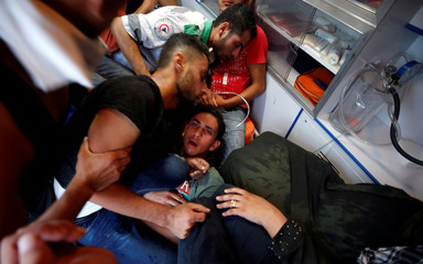 People tend to a Palestinian after inhaling tear gas during a protest calling for lifting the Israeli blockade on Gaza, near the maritime border with Israel, in the northern Gaza Strip