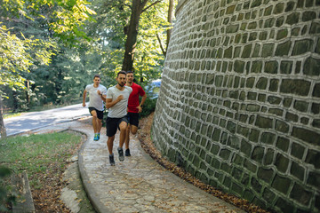 Three athletes running in the forest