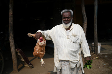 A man shows a chicken that he purchased at a market in Cox's Bazar