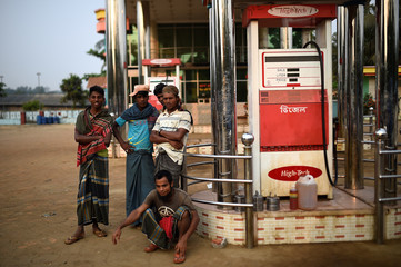 Men wait by a petrol station in Cox's Bazar