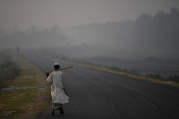 A man walks along a road during fog at dawn in Cox's Bazar