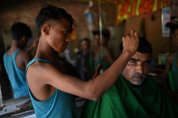 A man gets a hair cut at a barber shop in a market in Cox's Bazar